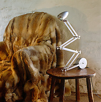 An interesting juxtaposition of textures and materials in this inviting corner of the living room with its fur-draped armchair and copy of a Marcel Breuer table lamp