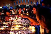 "Worshippers light candles to complement their prayers on wednesday evening at the Redemptorist Church in Baclaran in Manila, Philippines. The Baclaran church is said to be the most attended church in Asia drawing up to 100,000 worshippers "" in Manila, Philippines. Photo: Sanjit Das"