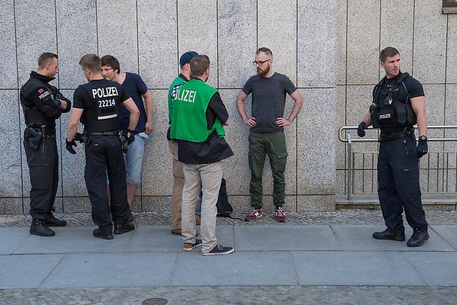 """Rechtsextreme """"Identitaere"""" versuchen Besetzung des Justizministerium.<br /> Am Freitag den 19. Mai 2017 versuchten ca. 40 Rechtsextremisten der sog. """"Identitaeren Bewegung"""" (IB) das Justizministerium zu besetzen. Sie setzten das Ministerium und den Justizminister Maas mit der Staatssicherheit der DDR gleich, hatten DDR-Fahnen dabei und trugen zum Teil DDR-Militaeruniformen.<br /> Die Neonazis scheiterten jedoch mit der Besetzung, da die Polizei im Vorfeld von der Aktion informiert war und rechtzeitig vor Ort war. Als die Polizei die Neonazis aufforderte zu gehen, legten die sich auf den Fußweg und skandierten """"Keine Gewalt"""" und Parolen gegen Fluechtlinge und fuer Deutschland. Daraufhin wurden die Neonazis einzeln abgefuehrt, durchsucht und erhielten einen Platzverweis.<br /> Im Bild: Robert Timm, Chef der Berliner """"Identitaeren"""" wird von Polizisten befragt.<br /> 19.5.2017, Berlin<br /> Copyright: Christian-Ditsch.de<br /> [Inhaltsveraendernde Manipulation des Fotos nur nach ausdruecklicher Genehmigung des Fotografen. Vereinbarungen ueber Abtretung von Persoenlichkeitsrechten/Model Release der abgebildeten Person/Personen liegen nicht vor. NO MODEL RELEASE! Nur fuer Redaktionelle Zwecke. Don't publish without copyright Christian-Ditsch.de, Veroeffentlichung nur mit Fotografennennung, sowie gegen Honorar, MwSt. und Beleg. Konto: I N G - D i B a, IBAN DE58500105175400192269, BIC INGDDEFFXXX, Kontakt: post@christian-ditsch.de<br /> Bei der Bearbeitung der Dateiinformationen darf die Urheberkennzeichnung in den EXIF- und  IPTC-Daten nicht entfernt werden, diese sind in digitalen Medien nach §95c UrhG rechtlich geschuetzt. Der Urhebervermerk wird gemaess §13 UrhG verlangt.]"""