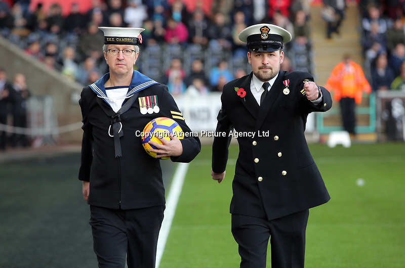 Members of the armed forces bring the match ball to the pitch during the Premier League match between Swansea City and Brighton and Hove Albion at The Liberty Stadium, Swansea, Wales, UK. Saturday 04 November 2017