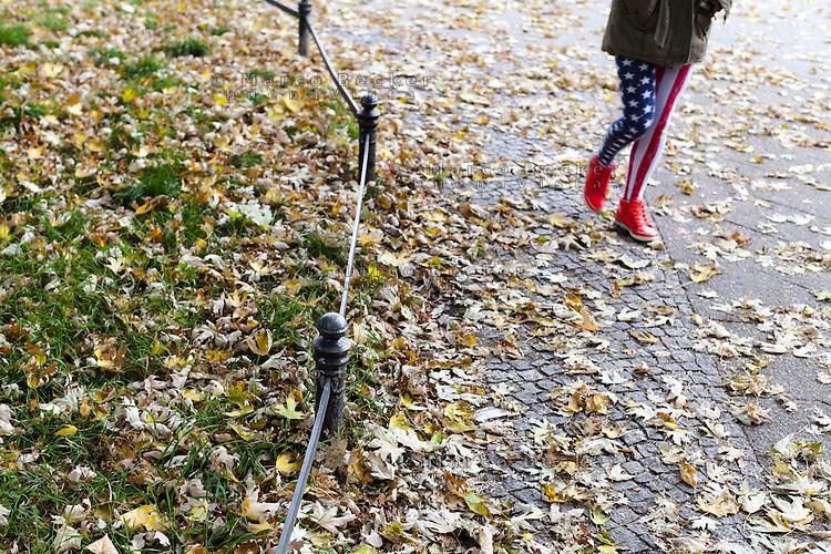 Berlino, quartiere Kreuzberg. Gambe di donna con indosso dei pantaloni a stelle e strisce e delle scarpe rosse, su un marciapiede coperto di foglie --- Berlin, Kreuzberg district. Woman's legs wearing pants with stars and stripes and red shoes, on a sidewalk covered with leafs