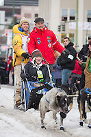 Alan Stevens and team leave the ceremonial start line with an Iditarider at 4th Avenue and D street in downtown Anchorage, Alaska during the 2015 Iditarod race. Photo by Jim Kohl/IditarodPhotos.com