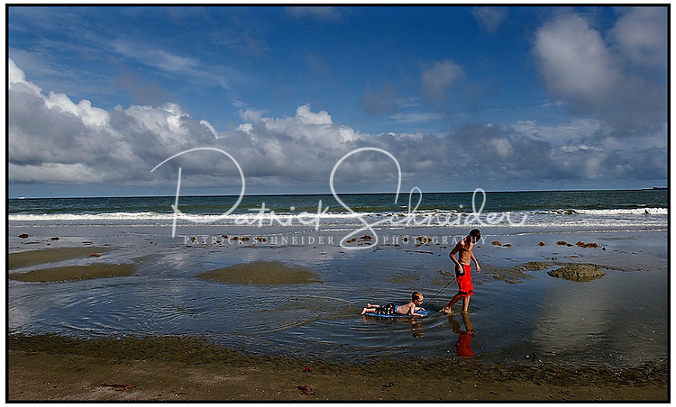 A boy pulls a younger boy on a boogie board through a tide pool. Photo taken on Sullivan's Island near Charleston, SC.  Model released image may be used to illustrate other destinations or concepts.