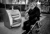 Switzerland. Canton Ticino. Lugano. An elderly man seats on his walker and smokes a cigarette. The city has organized large metal containers as garbage can. Some are used for recycling paper (carta), glass or aluminium. 8.01.2020  © 2020 Didier Ruef