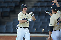 D.J. Poteet (4) of the Wake Forest Demon Deacons is greeted by his teammates after hitting a solo home run against the Gardner-Webb Runnin' Bulldogs at David F. Couch Ballpark on February 18, 2018 in  Winston-Salem, North Carolina. The Demon Deacons defeated the Runnin' Bulldogs 8-4 in game one of a double-header.  (Brian Westerholt/Four Seam Images)