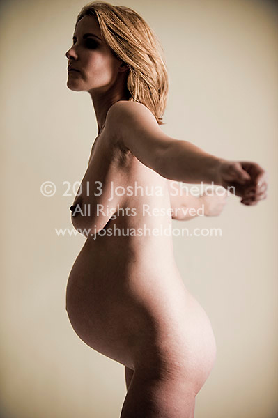Pregnant woman standing with arms in back of her