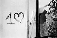 Switzerland. Geneva. Graffiti on a white wall. Black heart and a number one. A man with a ladder works as a caretaker. 13.12.12  © 2012 Didier Ruef