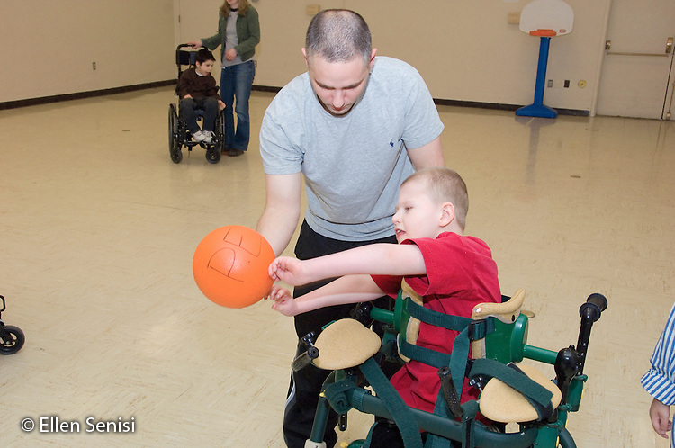 MR / Albany, NY.Langan School at Center for Disability Services .Ungraded private school which serves individuals with multiple disabilities.PE teacher helps child in gait trainer throw the ball during an Adaptive Physical Education class (APE). Boy: 9, cerebral palsy, non verbal with expressive and receptive language delays.MR: Pob1; Law4.© Ellen B. Senisi