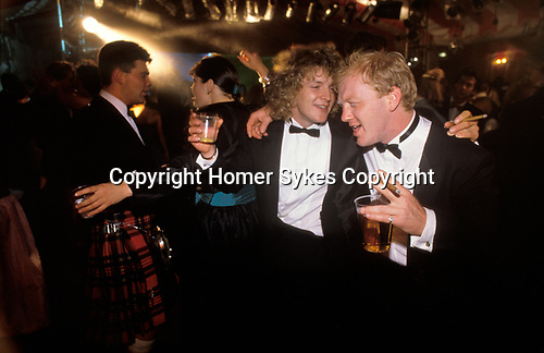 Cirencester, Gloucestershire. 1995 <br /> Tuxedoed young gents with cigars in hand and beer in plastic beakers do some drunken male bonding on the dance floor at the Royal Agricultural College annual end of year dance.