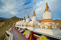 Prayer flags blowing in the breeze at the beautifully decorated chortens, Thiksey Gompa in Shey, Ladakh, India