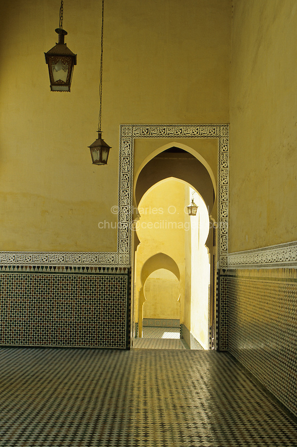 "Meknes, Morocco.  Mausoleum of Moulay Ismail.  Horseshoe Arch Doorway.  The Arabic inscription in the frieze surrounding the doorway reads ""'Auzu b'illah"", ""I seek refuge in God."""