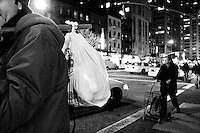 A successful find leads to a plastic bag packed full of food for one freegan while another trails with a still empty cart in New York City on April 5, 2006.