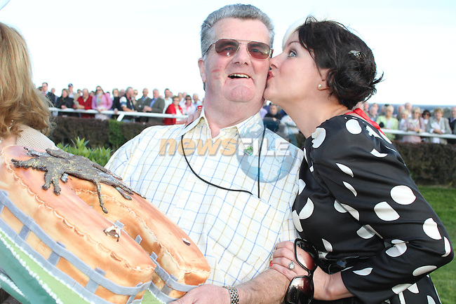 Chairman Jim Corcoran gets a kiss from Best Dressed Lady Competition Judge Triona McCarthy after being presented with a birthday cake from the committee at the Bellewstown Races....Picture Jenny Matthews/Newsfile.ie