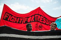 """Bis zu 5.000 Menschen kamen am Samstag den 5. Juli 2014 in Berlin zu einer Demonstration unter dem Motto """"Bleiberecht fuer Alle!"""". Aufgerufen zu der Demonstration hatten verschiedene linke und antirassistische Gruppen, nachdem ein Teil Kreuzbergs 10 Tage lang von etwa 1.000 Polizisten abgeriegelt worden war. Der gruene Baustadtrat Kreuzbergs hatte die Raeumung einer von Fluechtlingen besetzten leerstehenden Schule beantragt, wo gegen sich ca. 40 Fluechtlinge und Unterstuetzer zur Wehr gesetzt hatten. Die durch die Absperrungen betroffenen Anwohner der Schule hatten sich mit den Schulbesetzern solidarisiert. Sie wurden von der Polizei 10 Tage lang drangsaliert und konnten nur nach Abgabe ihrer Personalien ihre Wohnungen oder Arbeitsstaetten betreten.<br /> Die Demonstration wurde nach Polizeiangaben von bis zu 890 Beamten aus mehreren Bundeslaendern begleitet, mehrfach kam es zu Festnahmen von Demonstrationsteilnehmern.<br /> 5.7.2014, Berlin<br /> Copyright: Christian-Ditsch.de<br /> [Inhaltsveraendernde Manipulation des Fotos nur nach ausdruecklicher Genehmigung des Fotografen. Vereinbarungen ueber Abtretung von Persoenlichkeitsrechten/Model Release der abgebildeten Person/Personen liegen nicht vor. NO MODEL RELEASE! Don't publish without copyright Christian-Ditsch.de, Veroeffentlichung nur mit Fotografennennung, sowie gegen Honorar, MwSt. und Beleg. Konto: I N G - D i B a, IBAN DE58500105175400192269, BIC INGDDEFFXXX, Kontakt: post@christian-ditsch.de<br /> Urhebervermerk wird gemaess Paragraph 13 UHG verlangt.]"""