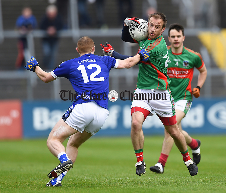 Conor Cooney of  Cratloe in action against Declan Callinan of Kilmurry Ibrickane during their senior football final replay at Cusack park. Photograph by John Kelly.