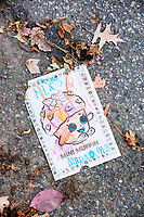 """A torn-out page from a coloring book with scribbled crayon markings and a picture of """"Mini Muffin"""" lays on the street on Orchard Street in Belmont, Massachusetts, USA, on Sat., Oct. 28, 2017."""
