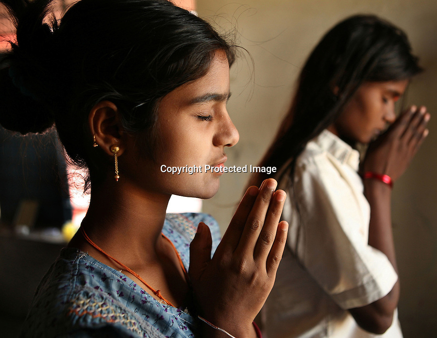 """Akshata Jivoji (left) and Malashri Kamble perform their morning prayers in their hostel room at Vimochana Sangha's school for the children of Devadasis in Malabad, India.  The school, which was founded in 1990 by Mr. B.L. Patil, is the first residential school established to break the cycle of the Devadasi system.  Because the belief is that all female children of Devadasis should themselves become Devadasis, the school was created to remove the children from the culture in which this practice took place and instead offer them an education.  All students receive free tuition, books, uniforms, food and medical care. Graduates have gone on to become teachers, nurses, engineers etc.  """"Most importantly, more than 300 girl chidren are married and living in the mainstream of society,"""" says Patil proudly.  """"This doesn't seem like an achievement for others but for us, this is proof that this generation has been prevented from following their mothers into the Devadasi system,""""."""