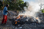 20 May 2019,Kwartu village East Java, Indonesia: Local rice farmer Kusen who has recently given up farming to become a plastic rag picker, tends a fire at a plastic rubbish dump in Kwartu village East Java outside Surabaya, Indonesia. Millions of tonnes of recyclable plastic trash from Australia and Europe is dumped for rag pickers to separate and sort. The plastics are used to fuel fires at local tofu factories among other industries. Australia is illegally sending non recyclable trash hidden within this lode and the Indonesian Government is cracking down on the practice and preparing to refuse to take Australia's rubbish that is creating enviromental and health issues locally. Picture by Graham Crouch/The Australian