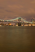 Manhattan Bridge and East River Illuminated at Night, showing lights of subway train crossing the bridge, New York City, New York State, USA