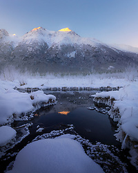 Sunrise light kisses the mountain peaks, reflected in a small pool surrounded by snow and hoar frost in Alaska.