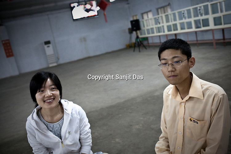25 year old Chinese interpreter, Yuan Lei (centre) seen with his girlfriend, Cui Yan (left) at the dining hall of the Chinese Colony in the Adani Power plant in Mundra port industrial city of Gujarat, India. Indian power companies have handed out dozens of major contracts to Chinese firms since 2008. Adani Power Ltd have built elaborate Chinatowns to accommodate Chinese workers, complete with Chinese chefs, ping pong tables and Chinese television. Chinese companies now supply equipment for about 25% of the 80,000 megawatts in new capacity.