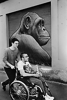 Switzerland. Canton Ticino. Lugano. A disabled young man seated in a wheelchair is being pushed by a friend on the sidewalk. A chimpanzee is drawn on a store's shutter. Chimpanzees (sometimes called chimps) are one of two exclusively African species of great ape that are currently extant. 24.05.2016 © 2016 Didier Ruef