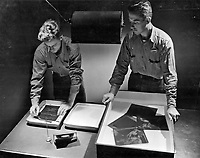 A student checks out on the processing of negative material by Tray development.  To the right is instructor E. F. Bauer, PhoM 1/c.  Class II students Advanced Ground Photography.