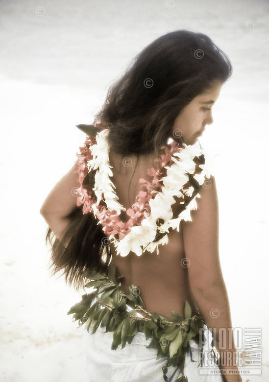 Polynesian woman at beach with leis draped over her back