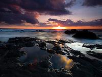 An amazing sunset sky reflects in tide pools along the dark rocky shoreline of Kohanaiki Beach Park (a.k.a. Pine Trees Beach), Big Island.