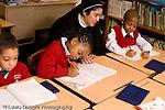 Parochial School Bronx New York  Kindergarten nun in habit working with child horizontal