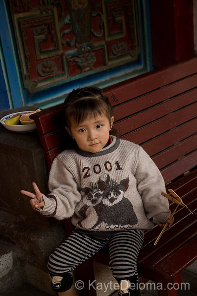 Serious pre-K girl gives the peace sign in front of her house in Old Town Lu Gang, Taiwan