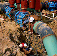 Workers inspect a series of connections and valves while installing a new gas pipeline across southern Arkansas. Arkansas.