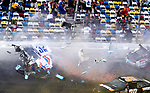 Spectators duck and shield themselves from debris from Kyle Larson's #32 Clorox Chevrolet as it  disintegrates from a wreck on the way to the finish line on the final lap of the NASCAR Nationwide Series DRIVE4COPD 300 auto race at Daytona International Speedway in Daytona Beach, Florida February 23, 2013. Twenty-nine spectators were injured in the stands.