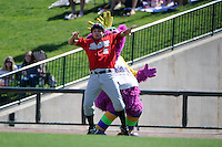 Great Lakes Loons guest Reggy the Purple Party Dude gropes an associate disguised as the first base coach during a game against the Fort Wayne TinCaps on August 18, 2013 at Dow Diamond in Midland, Michigan.  Fort Wayne defeated Great Lakes 4-3.  (Mike Janes/Four Seam Images)