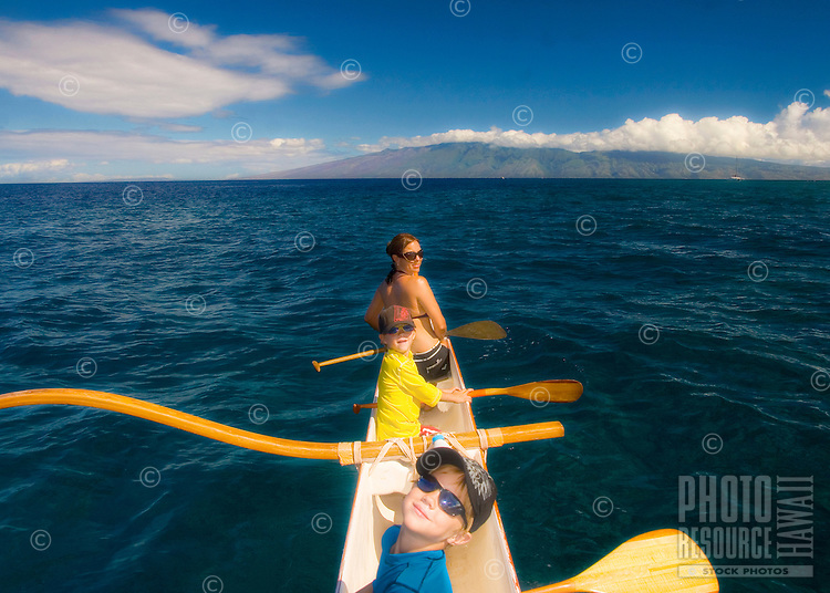 Woman and twin boys in a Hawaiian outrigger canoe off the coast of Maui with Moloka'i in the distance.