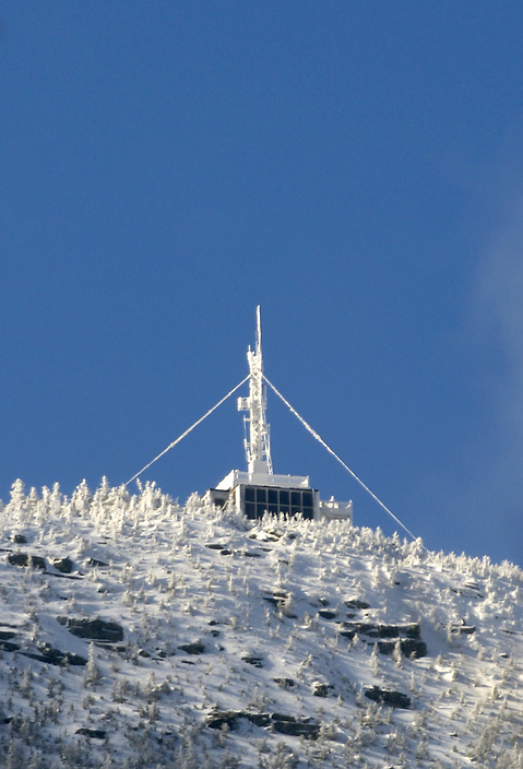 The observation deck on the summit of Cannon Mountain caked in rime ice, photographed from the floor of Franconia Notch with an extreme telephoto lens.
