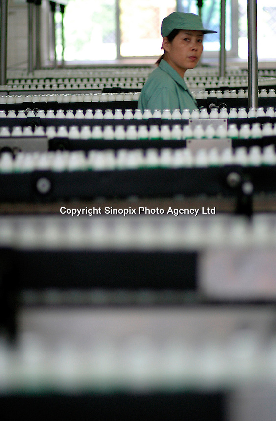 A woman inspects the dairy drink bottling line at the Wahaha Beverage Manufacturing Base in Hangzhou, China. The privately owned Wahaha group is the largest beverage manufacturer in China with a total production of 3.75 million tons in assorted beverages last year. The group has recently decided to ship nearly 15 thousand cases of its Future Cola to the U.S..07-JUN-04