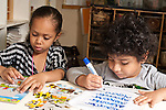 Education preschool 3-4 year olds boy and girl sitting side by side, girl playing with puzzle in cardboard frame, boy tracing his name with dry erase marker