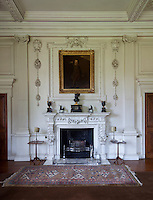 The fruiting baroque carvings on the original Georgian fireplace are repeated in the Edwardian plasterwork above, framing an 18th century portrait