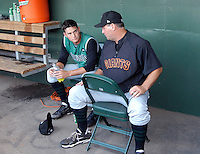 Pitching coach Steve Kline talks with starting pitcher Chris Heston (23) of the Augusta GreenJackets in a corner of the dugout after after a difficult inning of a game against the Greenville Drive on May 20, 2010, at Fluor Field at the West End in Greenville, S.C. Photo by: Tom Priddy/Four Seam Images