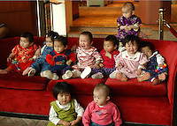 Adopted Chinese female babies pose for a group photograph at the 5-star White Swan Hotel in Guangzhou, China. Over 10,000 babies, all girls or disabled boys, are adopted from China annually.