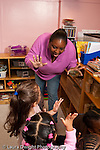 Education preschool 3-4 year olds female teacher doing counting activity with small group children holding up hands and fingers vertical