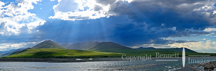Beams of sunlight illuminate the summer landscape after a rainstorm passes over the Kongakut River, in Alaska's Arctic National Wildlife Refuge.