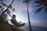 Man swinging in hammock with computer under palm trees at sunset
