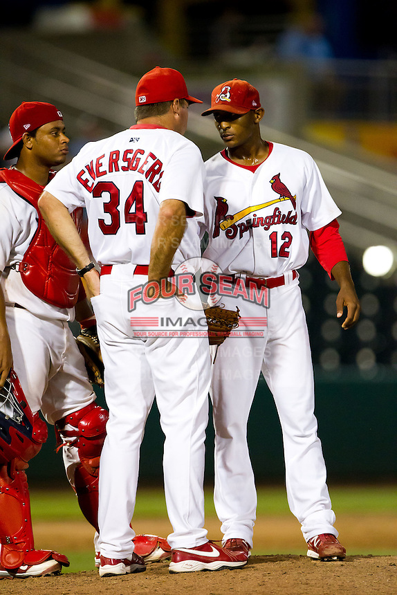 Samuel Freeman (12) of the Springfield Cardinals talks with pitching coach Bryan Eversgerd (34) on the mound during a game against the Tulsa Drillers at Hammons Field on July 19, 2011 in Springfield, Missouri. Tulsa defeated Springfield 17-11. (David Welker / Four Seam Images)