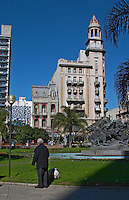 A late 19th century building in grandiose style on the Plaza Fabini Square. A man walking his dog in the park on the lawn grass and a statue with a fountain. Blue sky. Montevideo, Uruguay, South America