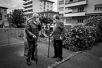 """Switzerland. Canton Ticino. Viganello. Two elderly men wear a mask on their face to protect themselves from the Coronavirus (also called Covid-19). They talk while meeting near a children playground. Due to the spread of the virus, the Federal Council has categorised the situation in the country as """"extraordinary"""". From March 16 the government ramped up its response to the widening pandemic, ordering the closure of shops. From April 27, they can reopen under very tight conditions. Life has started again. Old people go out again. Social distancing and masks. Viganello is a quarter of the city of Lugano. 8.06.2020  © 2020 Didier Ruef"""