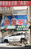 Cars crushed by the rubble of collapsed buildings in Dujiangyan, Sichuan, China..19 May 2008