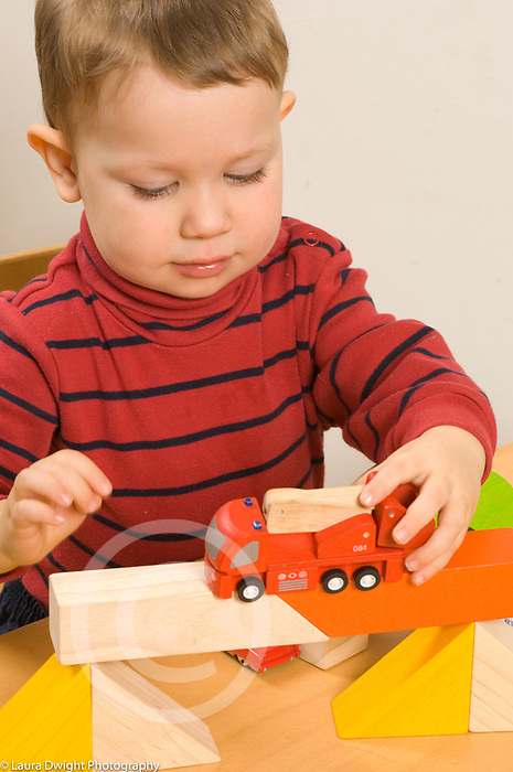 Two year old toddler boy pushing toy fire truck across bridge he made with blocks