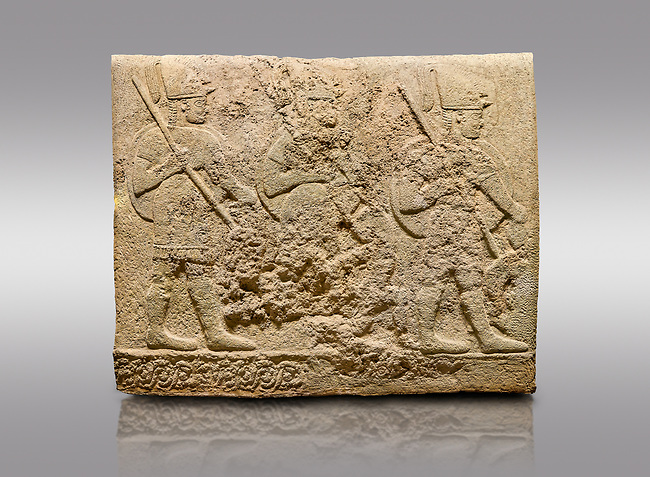 Picture & image of Hittite sculpted orthostats of Long Wall Limestone, Karkamıs, (Kargamıs), Carchemish (Karkemish), 900-700 BC. Anatolian Civilisations Museum, Ankara, Turkey<br /> <br /> Soldiers. Figure of three helmeted warriors. They have their shield in their back and their spear in their hand. The prisoners in their front are depicted as small. The lower part of the orthostat is decorated with wring / braiding motifs.<br /> <br /> On a gray background.